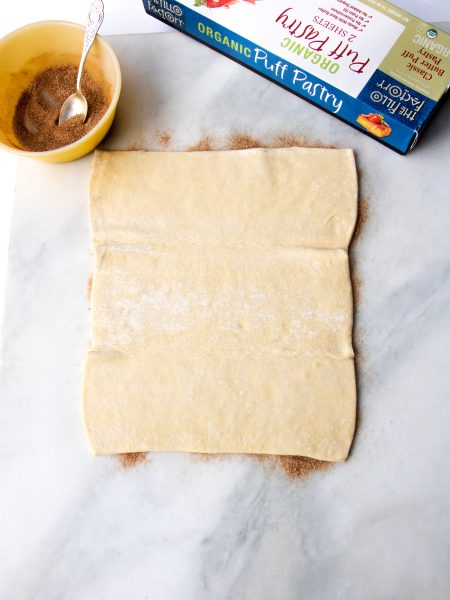 Puff pastry laying on top of cinnamon sugar
