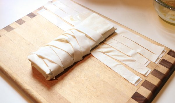Uncooked strudel is laid over fillo strips to show how to get a woven effect that is so pretty after baking