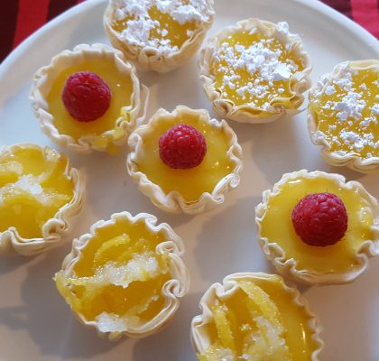 Fillo cups filled with lemon curd, dusted with confectioners sugar, and garnished with lemon zest.