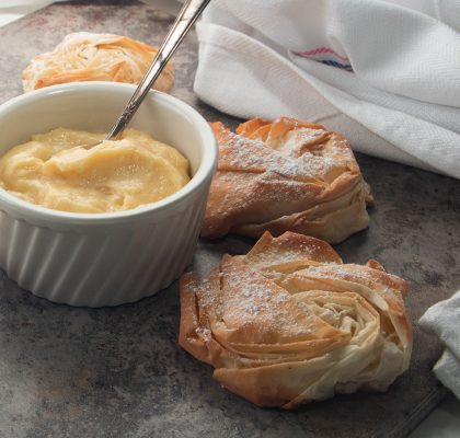 Fillo pastries on a gray stone background with a bowl of custard