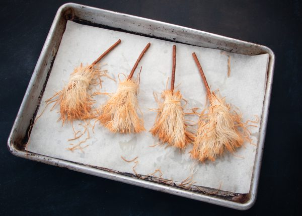 Edible brooms for halloween decoration in a baking pan.
