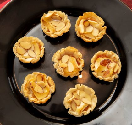 A black plate with mini fillo cups filled with warm sweet and creamy brie and apricots.